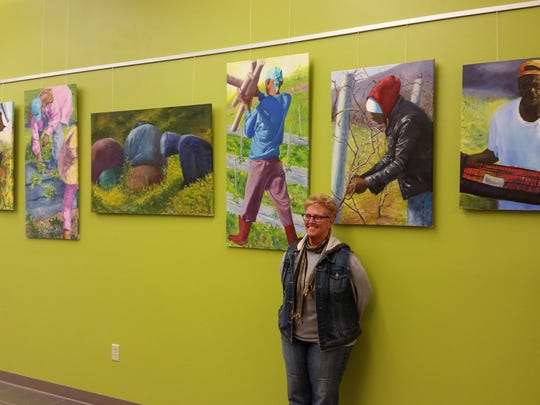 "Artist Barbara Masterson stands in front of her exhibit ""Migrant Workers"" at the Boardman Road Branch Library."
