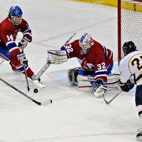 St. Cloud Apollo's Danny Wieber, Grady Ewing and goalie Nick Althaus are all there to stop a shot by Hermantown's Cole Koepke during the first period of the state Class A semifinals Friday at the Xcel Energy Center.