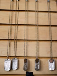 Military identification tags hang on a wall at the