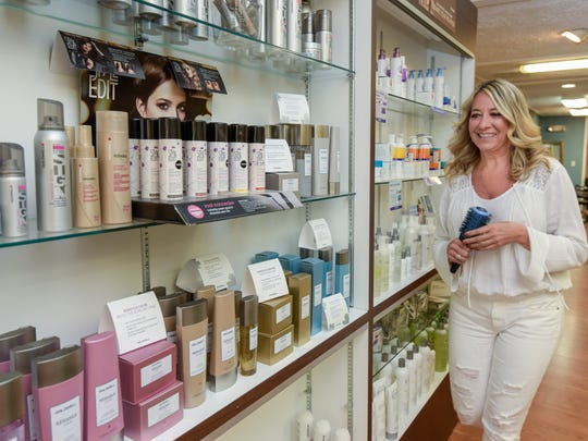 Hair stylist and color specialist Tina Marie Lisbona walks by a display of hair products at  Inspirations Hair and Nail Salon in Sea Girt.