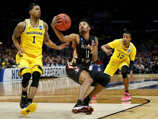 Florida State guard Braian Angola (11) shoots between Michigan guard Charles Matthews (1) and guard Muhammad-Ali Abdur-Rahkman (12) during the second half of an NCAA men's college basketball tournament regional final Saturday, March 24, 2018, in Los Angeles. (AP Photo/Jae Hong)