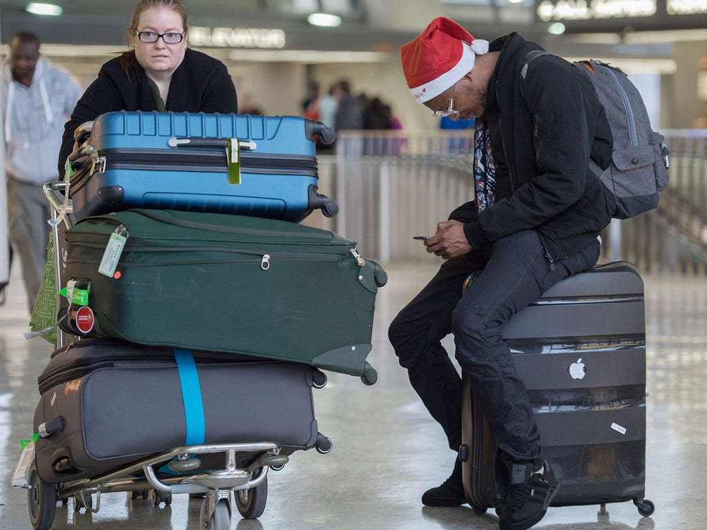 A woman pushes her luggage cart past a man focused on his smartphone on Dec. 23 at Dulles International Airport in Sterling, Va.