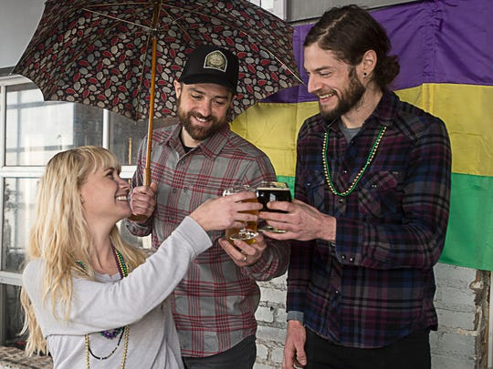 Burial Brewery owners Jess Reiser, left, and Doug Reiser, middle, along with brewer Tim Gormley, right, enjoy a beer Jan. 28. Burial's three-day Mardi Gras celebration begins Feb. 6, with each day featuring different food along with one of their three new brews - the Pecan Porter, the Mint Julep Blonde and the Hurricane IPA.