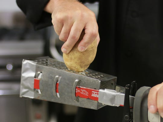 Chef Paul Smitala holds a potato against a powered kitchen tool in the Black Wolf Run kitchen Wednesday, Sept. 6, in Kohler.