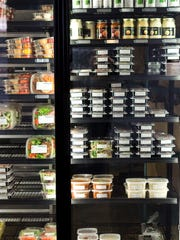A fridge of pre-made meals and other items are shown inside an Evolve Juicery and Paleo Kitchen.