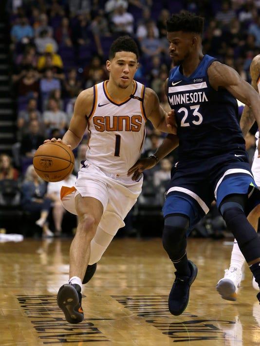 Phoenix Suns guard Devin Booker (1) drives on Minnesota Timberwolves guard Jimmy Butler in the second half during an NBA basketball game, Saturday, Nov 11, 2017, in Phoenix. The Suns defeated the Timberwolves 118-110. (AP Photo/Rick Scuteri)