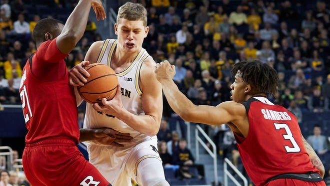Michigan Wolverines forward Moritz Wagner (13) dribbles defended by Rutgers Scarlet Knights forward Mamadou Doucoure (21) and guard Corey Sanders (3) in the first half at Crisler Center.