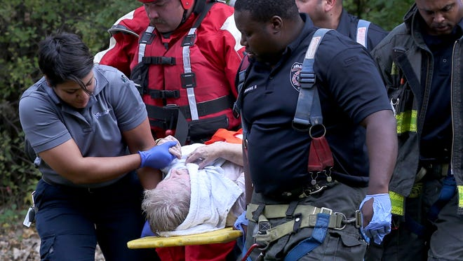 Rural Metro EMT, Yesenia Cintron, holds the hand of the elderly woman rescued from the Genesee River after she was car jack at her home in Gates.