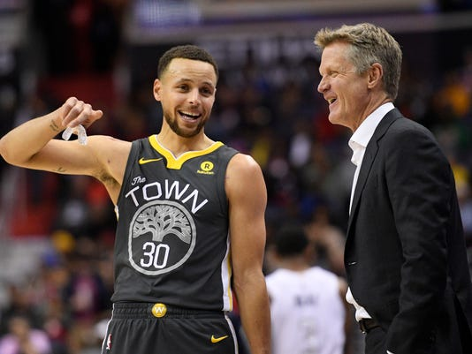 Golden State Warriors guard Stephen Curry, left, laughs with Warriors cach Steve Kerr during the first half of the team's NBA basketball game against the Washington Wizards, Wednesday, Feb. 28, 2018, in Washington. (AP Photo/Nick Wass)
