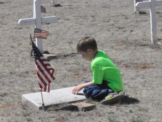 A young boy sits at the grave of a veteran at Fort