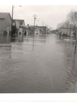 Floodwaters sweep downtown Mishicot in early 1966.