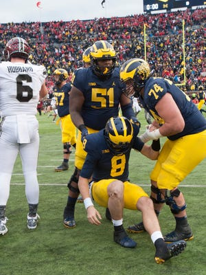 Michigan offensive linemen Cesar Ruiz (51) and Ben Bredeson (74) pick quarterback John O'Korn up off the turf after he was sacked by Ohio State defensive end Sam Hubbard on the final play of the game.