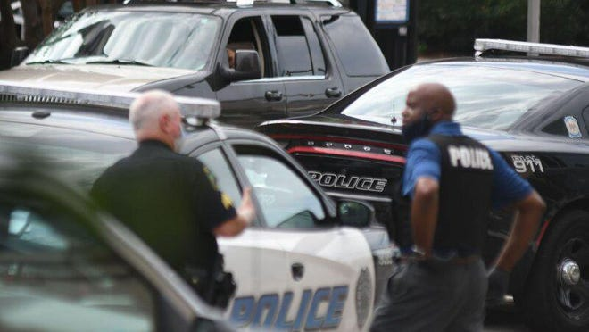 Members of the Wilmington Police Department and the New Hanover County Sheriff's Office surround a man in a car in front of Wilmington City Hall Wednesday, July 1, 2020. Police received an anonymous tip that the man was threatening to incite violence and the officers were attempting to talk him out of his car.