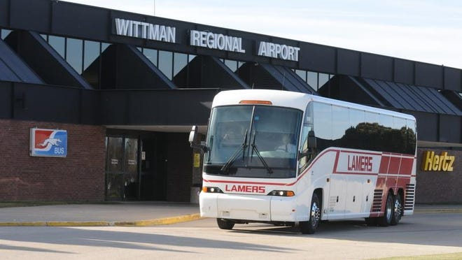 A coach bus parks in front of the Wittman Regional Airport terminal in Oshkosh in this 2013 file photo.