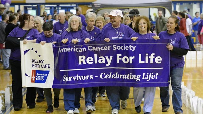 Cancer survivors walk evening during the 2013 Baxter County?s Relay for Life at the Mountain Home High School gymnasium. Weather forced last year's event indoors. More than $40,000 was raised for the American Cancer Society.
