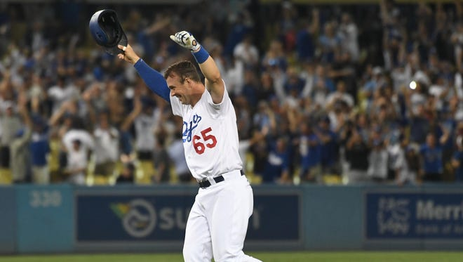 Los Angeles Dodgers pinch hitter Kyle Farmer (65) celebrates after hitting a walk-off double against the San Francisco Giants in the 11th inning at Dodger Stadium.