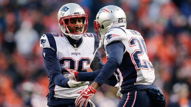 New England Patriots defensive back Eric Rowe (25) celebrates with cornerback Logan Ryan (26) after a play in the third quarter against the Denver Broncos at Sports Authority Field at Mile High.