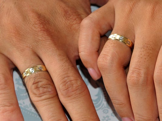 A couple holds hands showing their weddi