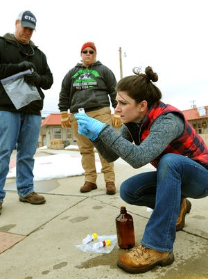 Environmental Protection Agency contractor Megan Adamczyk checks a water sample in Glendive, Mont., as water is drained from fire hydrants, Wednesday, Jan. 21, 2015. Workers recovered about 10,000 gallons of oil from a ruptured pipeline that spilled crude into Yellowstone River and contaminated the drinking water supply of the eastern Montana city downstream.  An estimated 40,000 gallons is still in the river and will be difficult to remove because of a thick layer of ice. (AP Photo/The Billings Gazette, Larry Mayer )