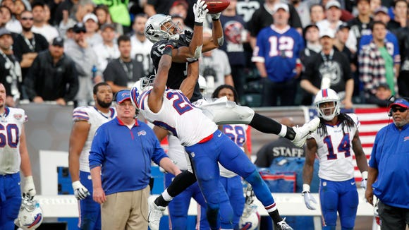 Oakland's Andre Holmes catches a 51-yard pass over Bills cornerback Corey Graham to help the Raiders shock the Bills.