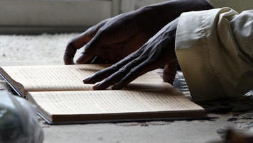 A man follows along in the Quran during an afternoon prayer at the mosque in a Lockland apartment complex that houses Fulani people, Saturday, August 20, 2011.