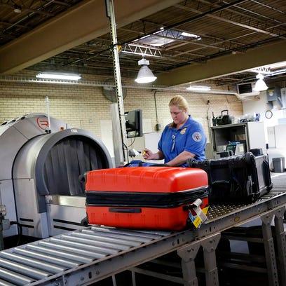An Elmira Corning Regional Airport employee scans and