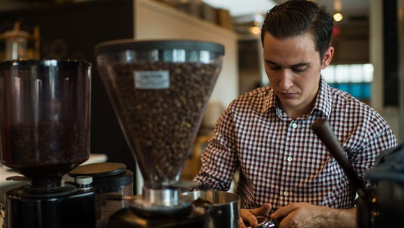 Co-owner Nathanael Johnson presses coffee grinds into