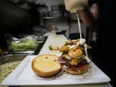 Assistant kitchen manager Taylor Randall applies the finishing sauce onto a Surf 'n Turf burger on Tuesday, March 6, 2018, at Stuft - A Burger Bar in Old Town Fort Collins, Colo.