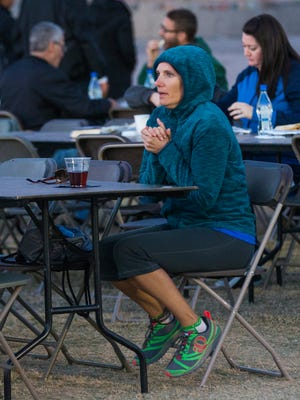 Cheryl Stadlman tries to stay warm while waiting for a dinner for Ironman volunteers Monday at Tempe Beach Park.