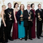 """In this Sept. 18, 2015 photo, """"Downton Abbey"""" cast members, writers and producers pose with their first Emmys for outstanding writing and outstanding miniseries or movie at the 63rd Primetime Emmy Awards."""