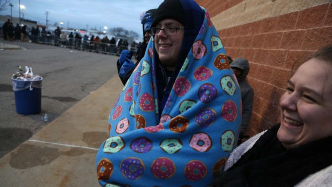 From left, Jake Apfel and his sister Alysha Apfel have a laugh as Jake keeps warm with her donut blanket as they both wait in line with close to 400 other people on Thanksgiving at Best Buy on John R. Road in Madison Heights.