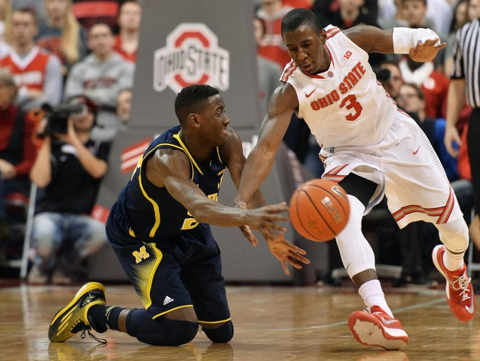 Michigan's  Caris LeVert  passes off the ball before
