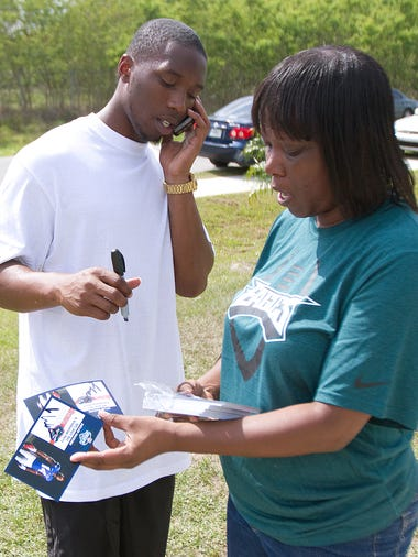 Former Cape Coral High football player Jaylen Watkins autographs cards with his mother Brandy Green outside their home Saturday in Fort Myers. Watkins was chosen by the the Philadelphia Eagles in the fourth round of the NFL Draft on Saturday.