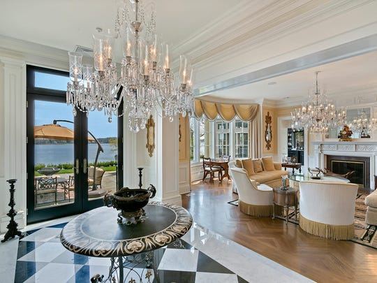 The foyer and living room have lavish crystal chandeliers.