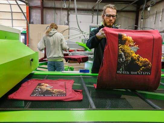 Danny Kimball lays freshly screen printed t-shirts
