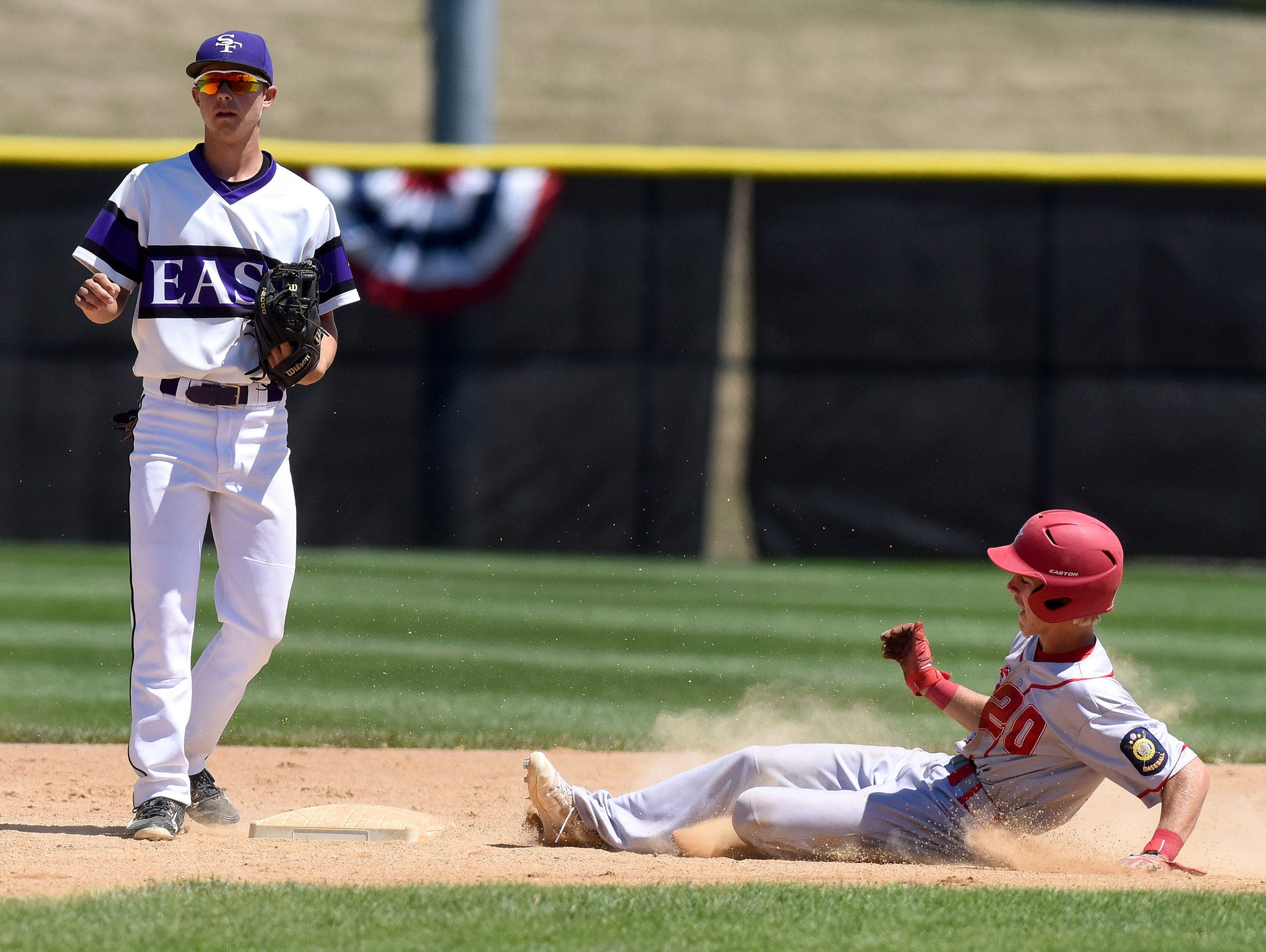 Rapid City Post 320's Connor Burgess slides into second base while Sioux Falls East Post 15's Matt Hedeen waits for the ball during the American Legion Class A Baseball State Tournament at Harmodon Park on Saturday afternoon.