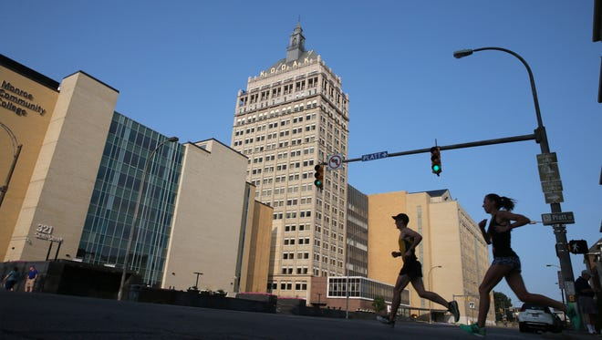 Runners in the half marathon cross State Street as they race past the Kodak tower toward the finish line.