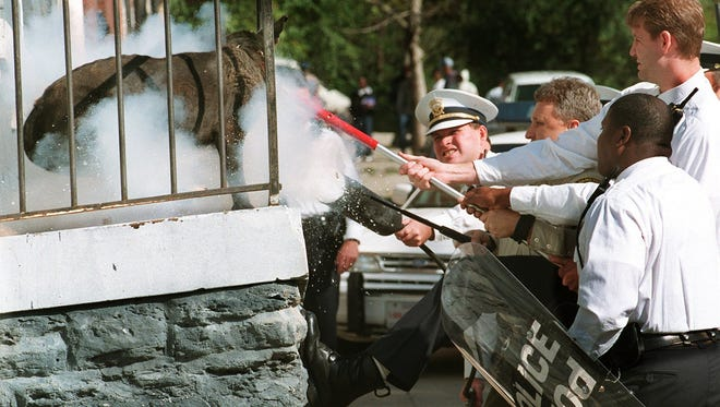 In this 1997 file photo, Hamilton County SPCA officials and Cincinnati police restrain a vicious dog, Fathead, on a porch with a harness and a fire extinguisher after the dog attacked several people on Mulberry St. in Over-the Rhine. Police and fire officials at the scene said they had been to this address before and that the same dog had bitten other people.
