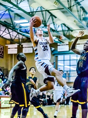 Okemos' Atticus Bohr, center, drives to the basket to lay the ball in past Waverly's Emmanuel Gildo.