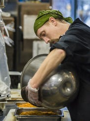 Alex Barrett pours a large bowl of mashed butternut