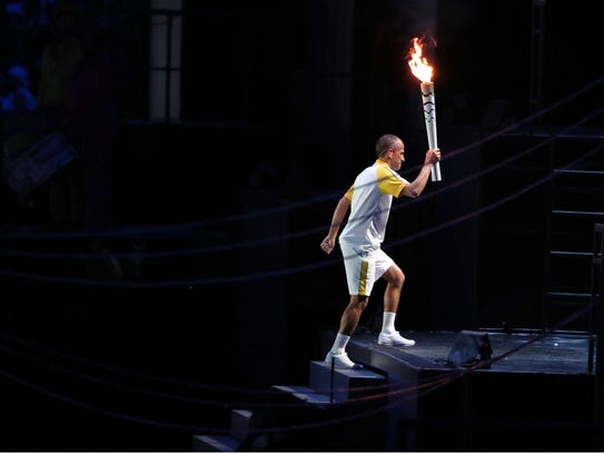 Vanderlei Lima lights the caldron during the opening