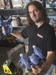 Chris Cardillo shows a pair of retro anime robots, part of his toy collection at his home in Medford.