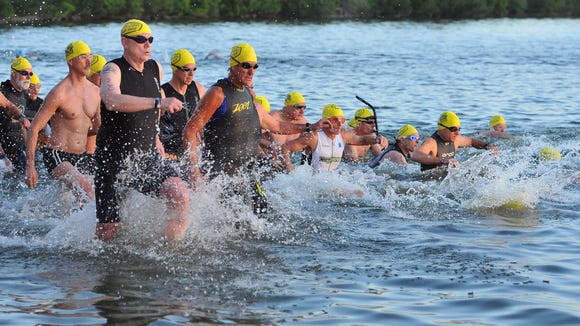 Triathletes head out for the swim portion in the lagoon during the Ron Jon Cocoa Beach Triathlon Sunday.
