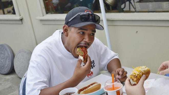 Juan Cortez of Visalia bites into his hot dos at Saturday's Three Rivers Hot Dog Festival. The event raised money for the Three Rivers Historical Museum and to purchase equipment for Tulare County Fire Station 14 in the town.