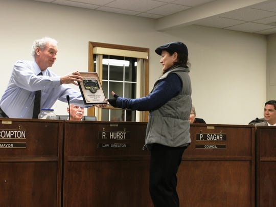Pataskala Mayor Mike Compton hands resident Ann Walther a Behind the Scenes Citizen of the Year award. Compton recognized Walther for her work with the Pataskala Recreation Association, a non-profit group that helped save the city's pool, among other parks-related undertakings.