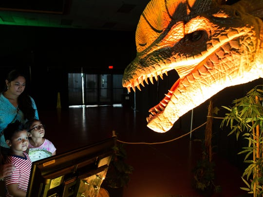 Five-year-old Jordan Lopez and eight-year-old Alice Rodriguez look up at a dilophosaurus during Discover the Dinosaurs at the American Bank Center, Saturday, July 2, 2016.