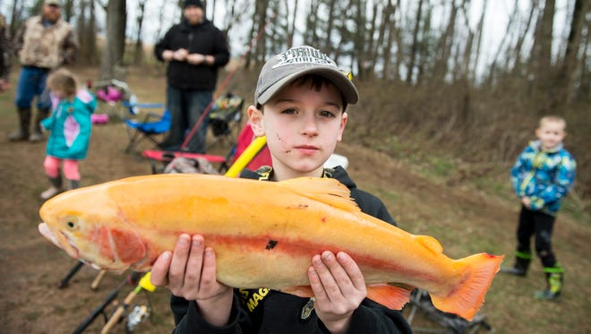 Lucas Link, 8, holds up a 23-inch palomino trout he caught while fishing at Kaiser Lake in New Oxford during the first day of trout season on Saturday.