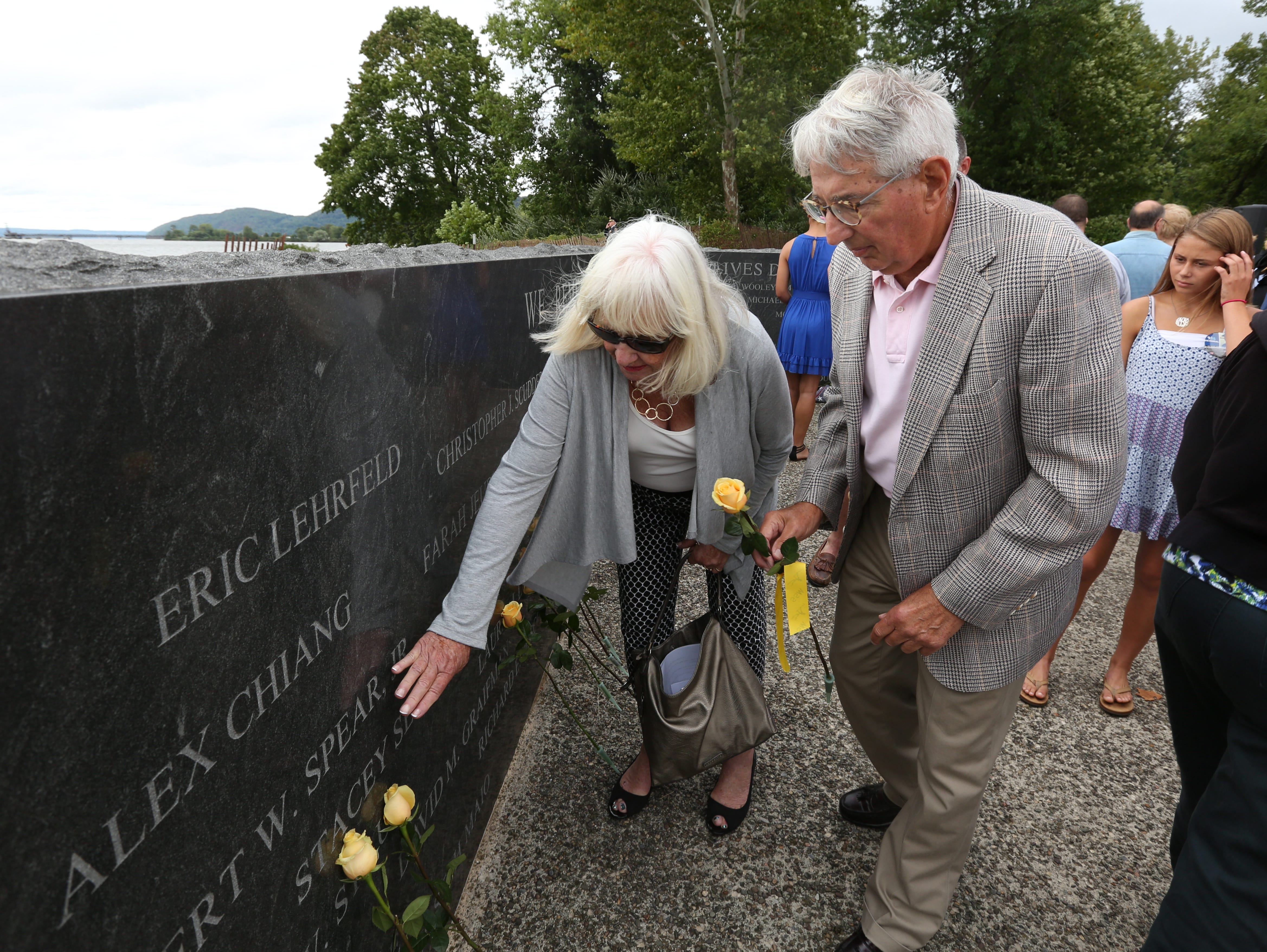 Fran and Semo Sennas place a flower in memory of their daughter, Stacey Sennas McGowan during the Rockland County Sept. 11 Memorial Service in Haverstraw Bay Park.