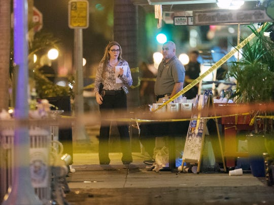 Law enforcement officials investigate a fatal shooting at Zombicon in downtown Fort Myers on Oct. 17, 2015.