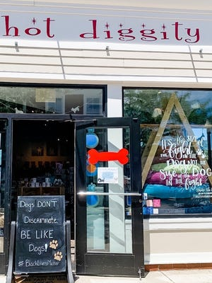 Ashley Carr posted this sign June 3 outside her Hot Diggity dog boutique in Mashpee Commons. A recent complaint to Mashpee Commons management about the message prompted Carr to remove the sign Friday, but an outpouring of public support and encouragement from the management team led Carr to replace the sign Saturday.